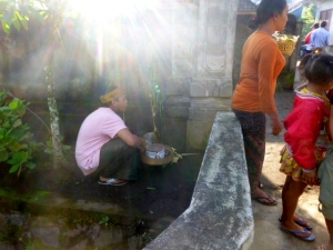 Ketut places offerings by one of the temporary altars